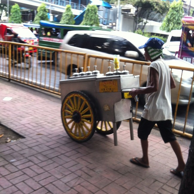 A Sorbetero peddling his colorful cart around the city.
