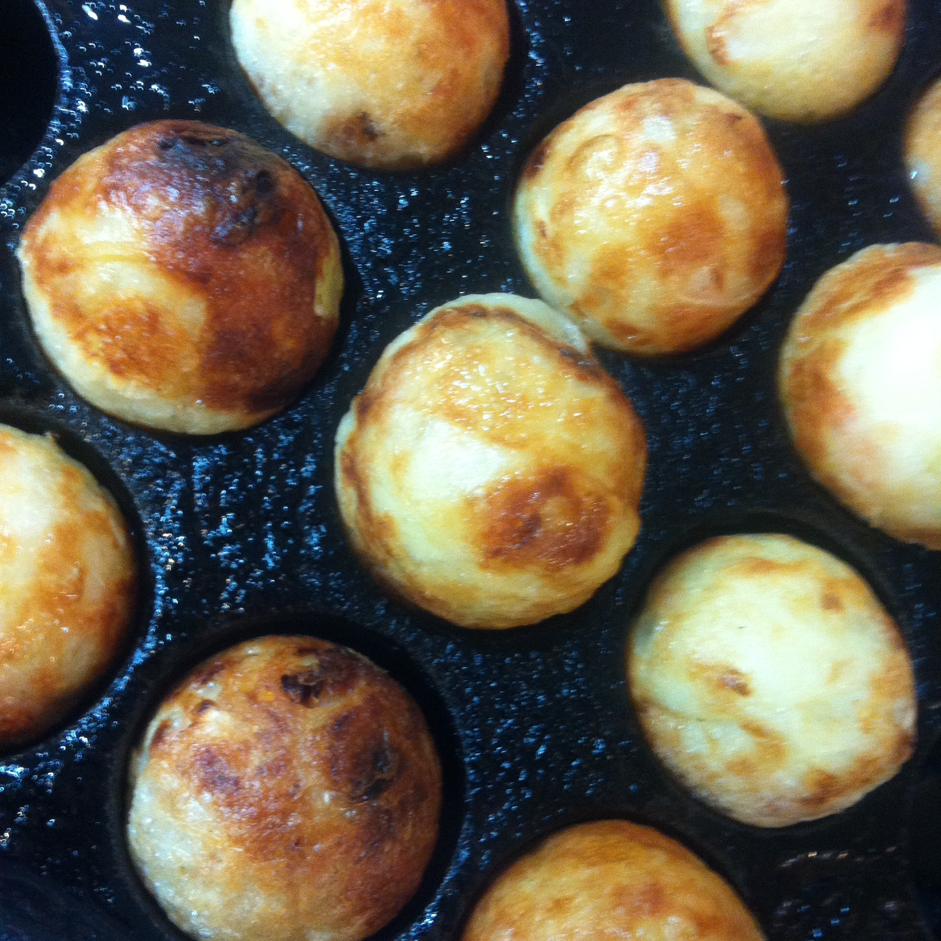 Takoyaki being prepared in the pan.