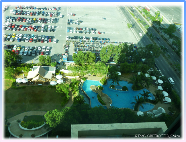 A VIEW OF THE POOL AREA FROM A ROOM.