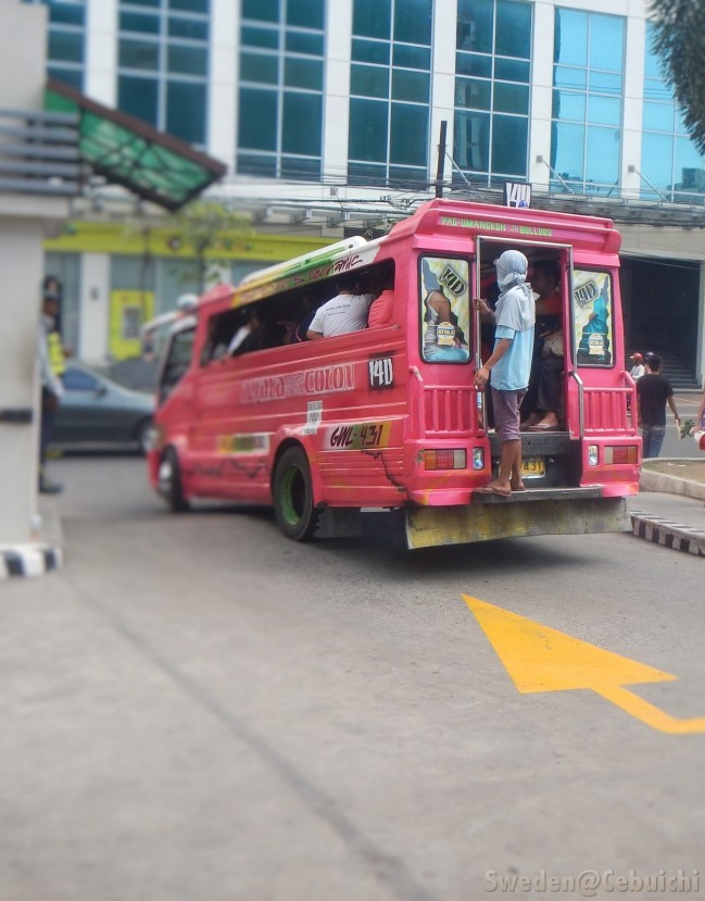 A Konduktor is often seen at the back of the jeepney.