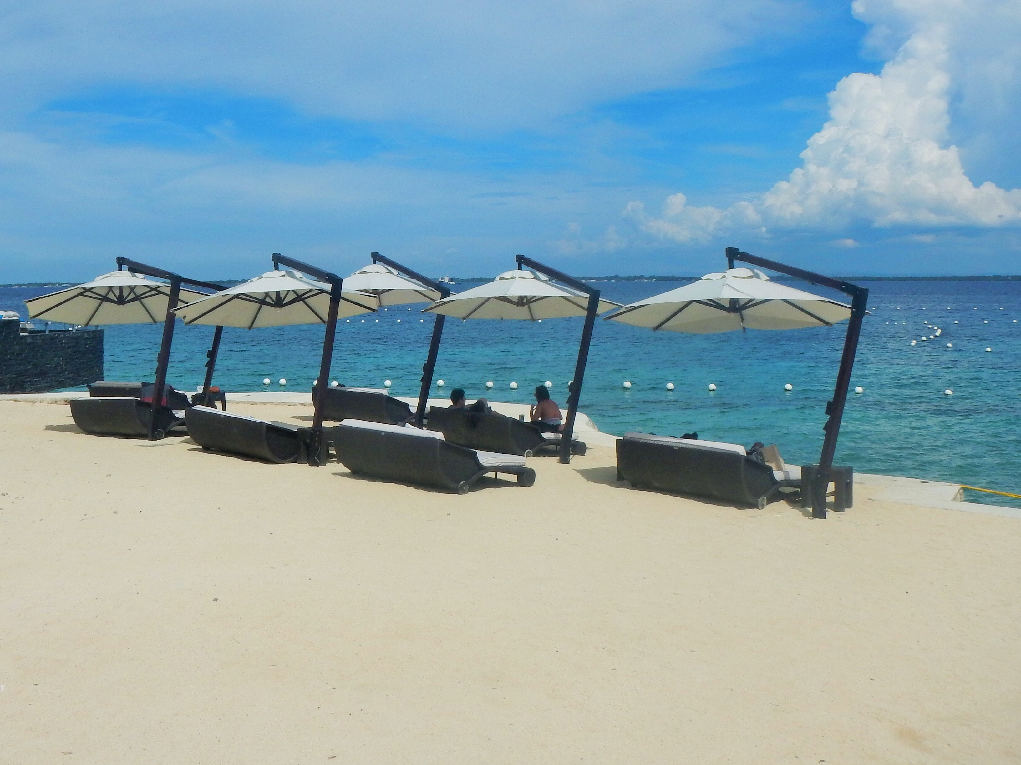 Relax and enjoy the breathtaking view on a hot, sunny day with these parasol-protected lounging chairs.